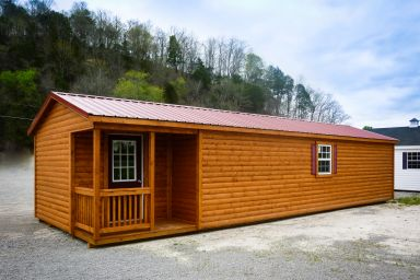 A prefab cabin in Tennessee with log siding and a corner porch