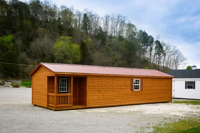 A prefab cabin in Tennessee with log siding and a red metal roof