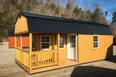 A small cabin for sale in Kentucky with wooden siding and a wraparound porch