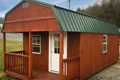 A small cabin for sale in Kentucky with wooden siding and a loft