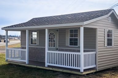 A portable cabin for sale in Kentucky with vinyl siding and a porch