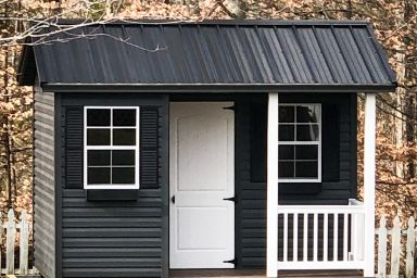 A portable cabin for sale in Tennessee with black vinyl siding and a porch