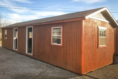 A portable cabin for sale in Tennessee with wooden siding and two doors