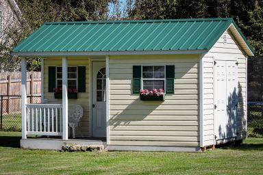 A portable cabin in Kentucky with a corner porch and a green metal roof