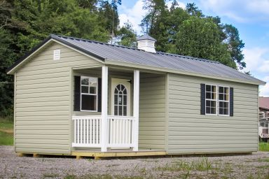A portable cabin in Tennessee with a metal roof and a cupola