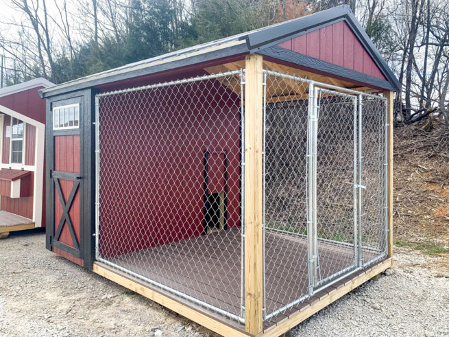 A red and black outdoor dog kennel for sale in Kentucky with wooden siding