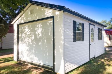 A small portable garage in Tennessee with white vinyl siding and two windows