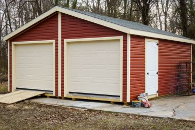 A prefab two-car garage in Kentucky with red vinyl siding