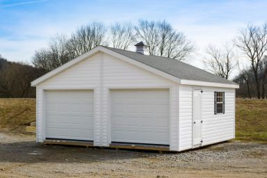 A prefab two-car garage in Kentucky with vinyl siding and a cupola